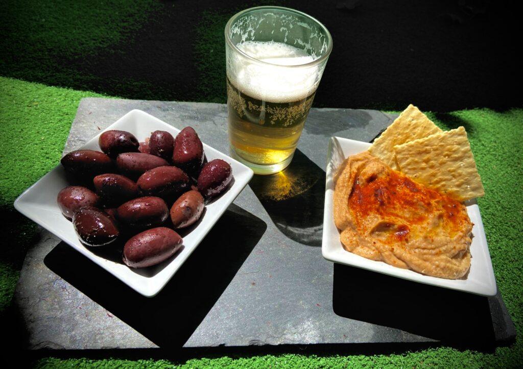 Tapa de hummus de aceituna, aceitunas kalamata y cerveza